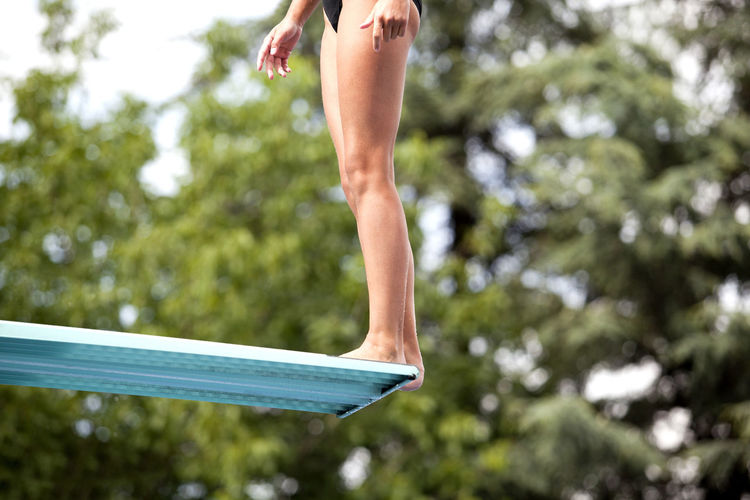 Female high diver standing on a springboard, preparing to dive Diving Jump Recreation  Woman Dive Diving Board Female Fitness Girl Human Leg Human Legs Leisure Activity Lifestyles Nature Outdoors Pool Sport Sports Springboard Springboard Diver Summer Swimming Pool Tree Vacation