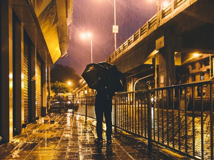 Rear view of man with umbrella on footpath at night
