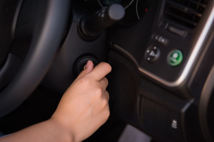 Cropped hand of woman adjusting air conditioner button in car