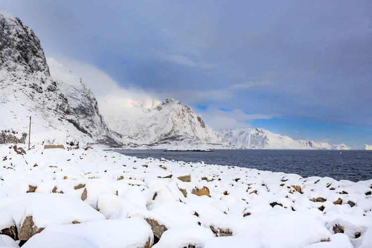 Scenic view of snowcapped mountain by lake against cloudy sky