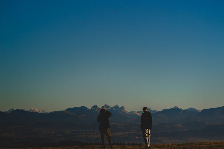 Rear view of men looking at mountains against clear blue sky