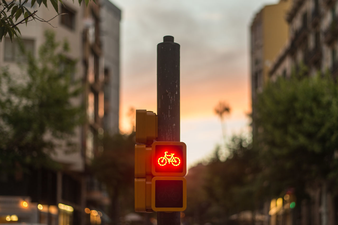 Bicycle Sign On Pole In City Against Sky During Sunset