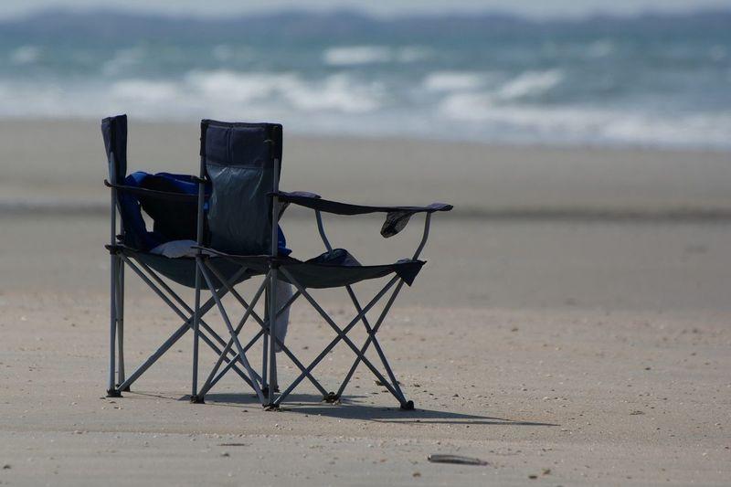 Folding chairs on sandy beach