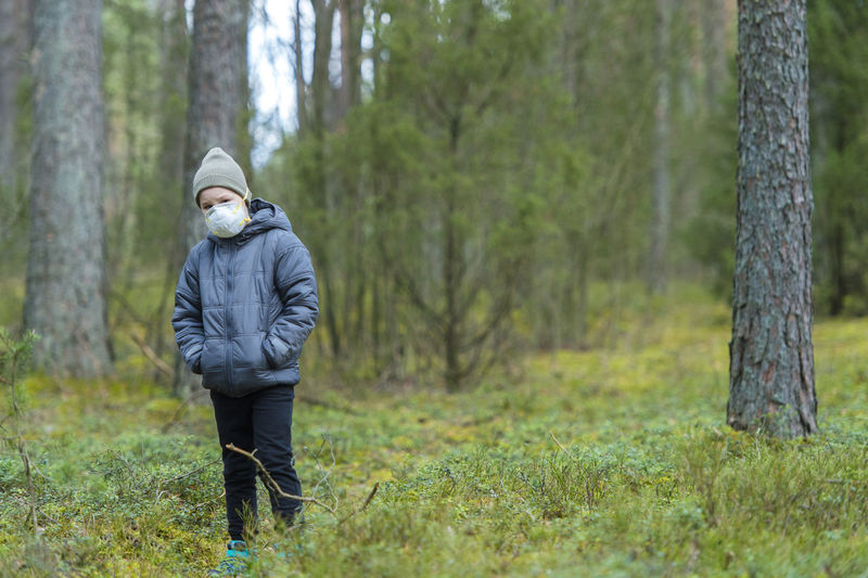 Girl wearing hooded jacket and mask standing in forest