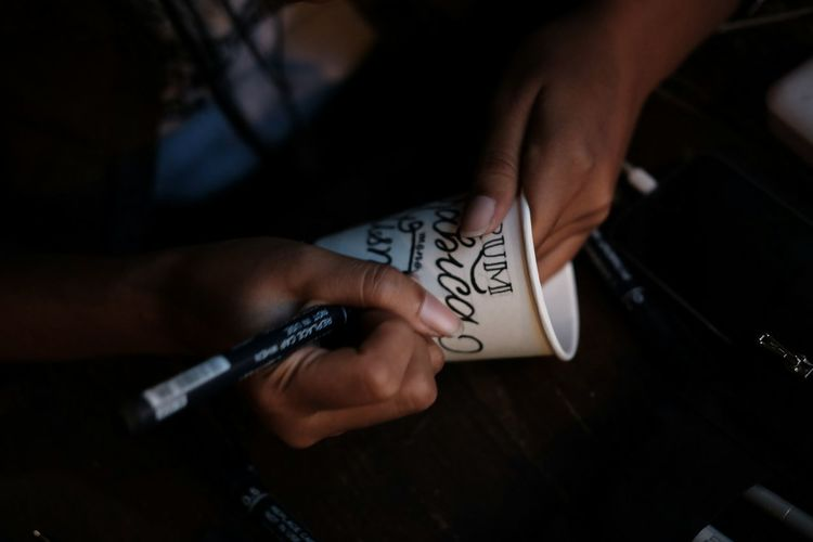 Midsection of woman writing on disposable cup