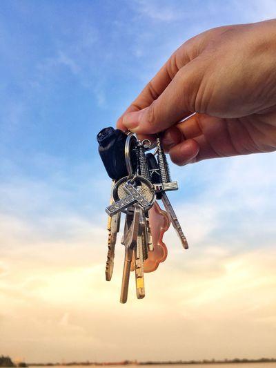Cropped hand holding keys against sky