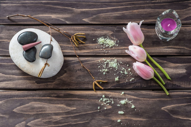 Close-Up Of Pebbles With Tea Light Candle And Tulips On Table
