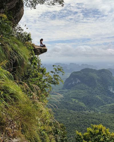 Woman sitting on mountain against cloudy sky