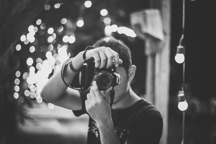 Portrait Of Young Man Photographing Illuminated Camera