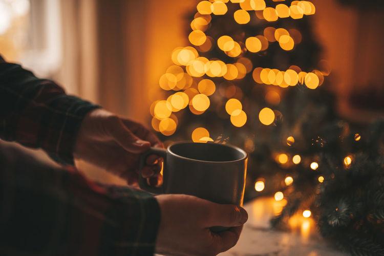 Man holding coffee cup on christmas tree