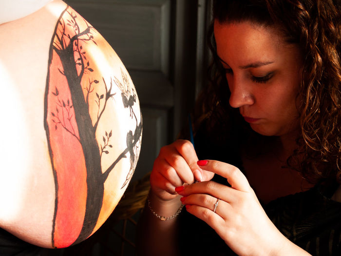 Friend making painting on pregnant woman stomach at home