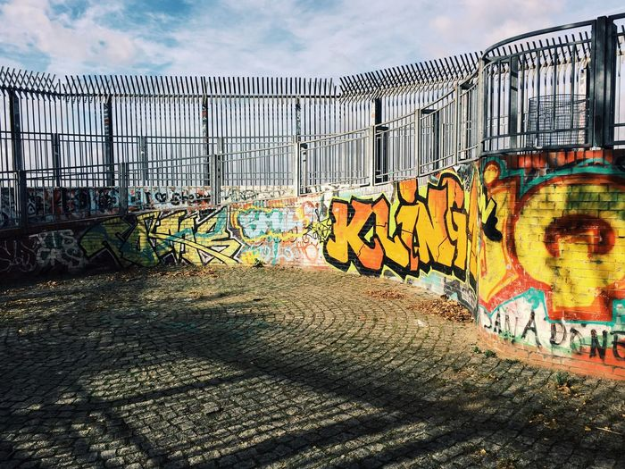 Graffiti on metal bridge against sky