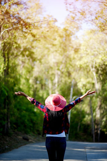 Rear view of woman with arms outstretched standing against trees