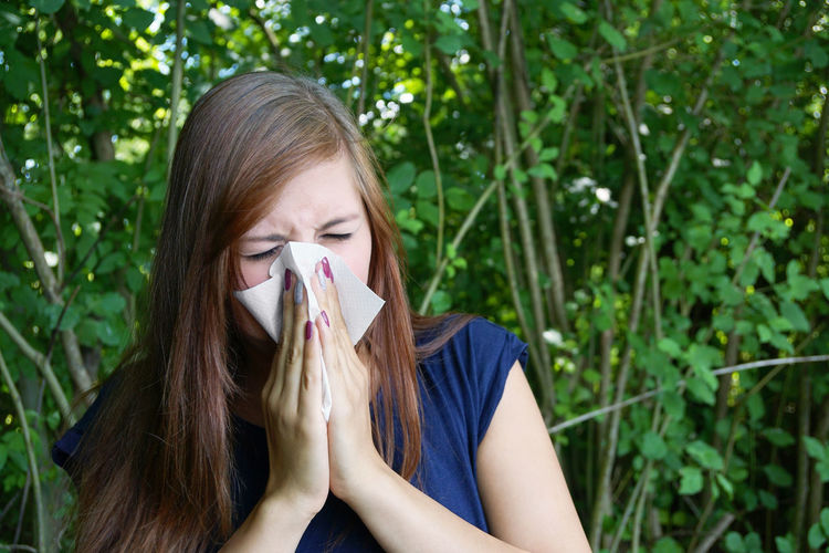 Allergic Allergy Blowing Nose Brown Hair Casual Clothing Cold Day Girl Hayfever Headshot Health Lifestyles Long Hair Outdoors Paper Tissue Person Portrait Real People Sneezing Sniffles Tissue Wiping Nose Woman Young Adult Young Women