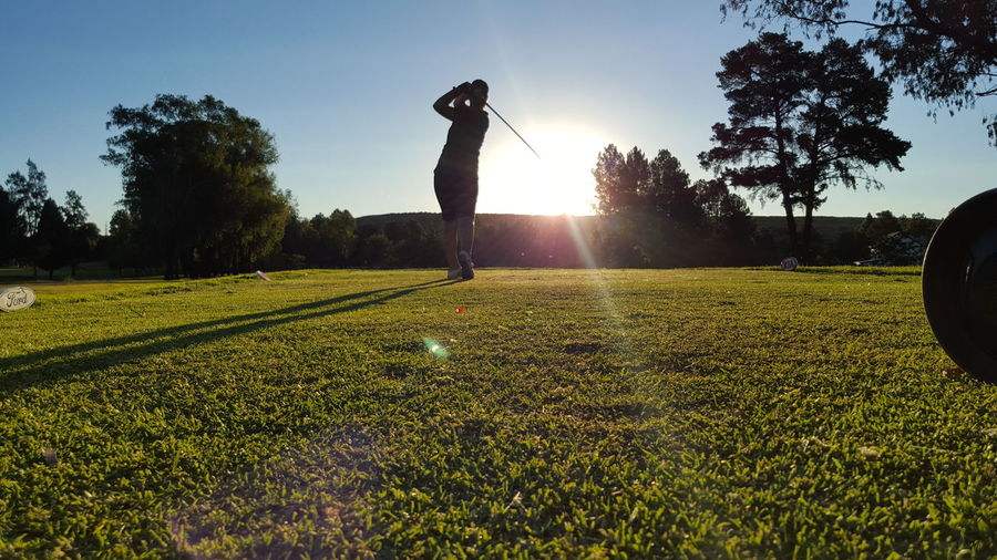 Low angle view of woman at golf course against sky during sunny day