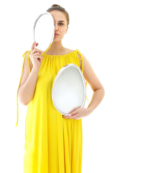 Woman holding yellow while standing against white background