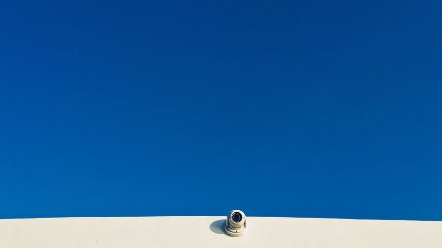 Low angle view of security camera on wall against blue sky