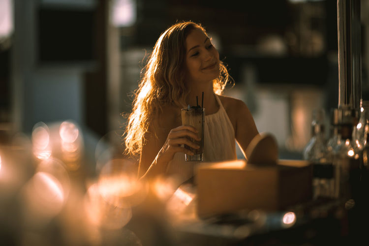 Young woman having drink at bar counter during sunset