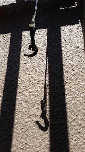 High angle view of old iron hook and shadow