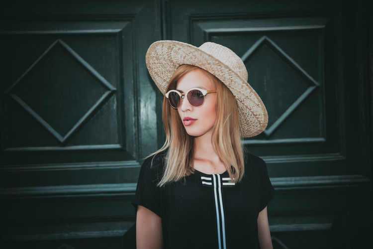 Woman in sunglasses and hat standing against door