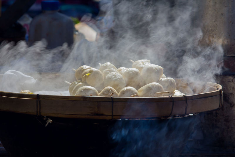 Close-up of steam emitting from dumplings in container