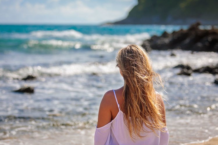 Young beautiful girl by the sea with developing hair