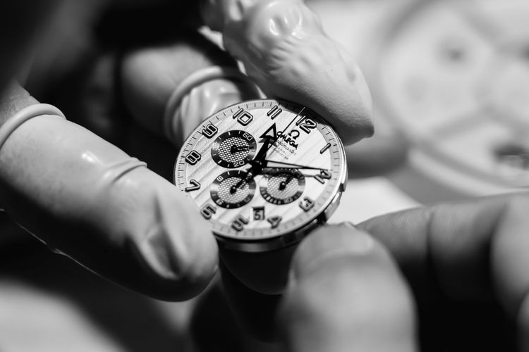 Close-up of hand holding clock