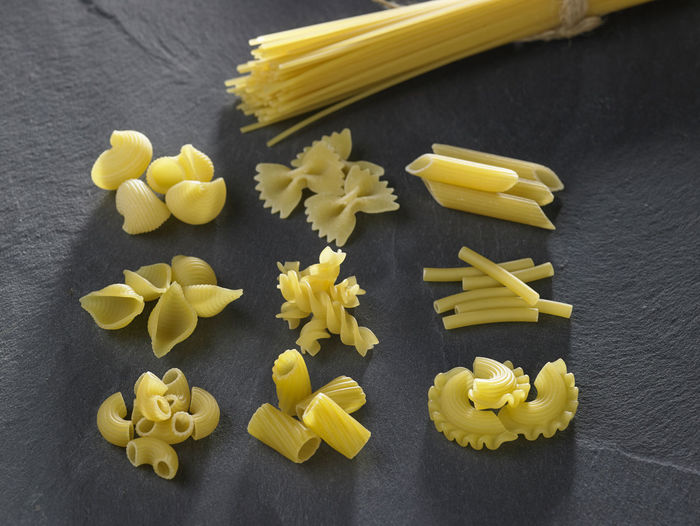 Variety of types and shapes of Italian pasta Black Background Dried Food Food And Drink Freshness Spaghetti Assortment Carbohydrate - Food Type Choice Directly Above Food Freshness Healthy Eating High Angle View Italian Food Large Group Of Objects Macaroni No People Pasta Raw Food Slate Still Life Studio Shot Variation Variety Yellow