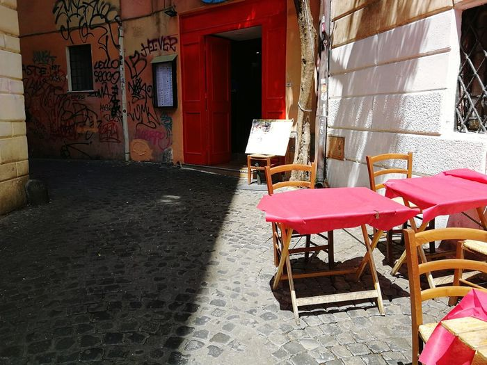 Empty chairs and tables outside building