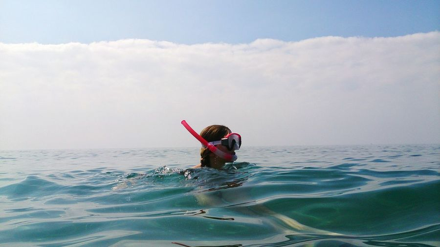 Woman With Snorkel Swimming In Sea Against Cloudy Sky