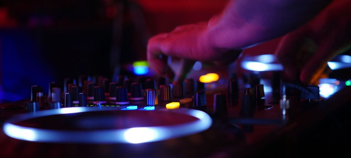 Cropped hand of dj adjusting knobs on sound mixer