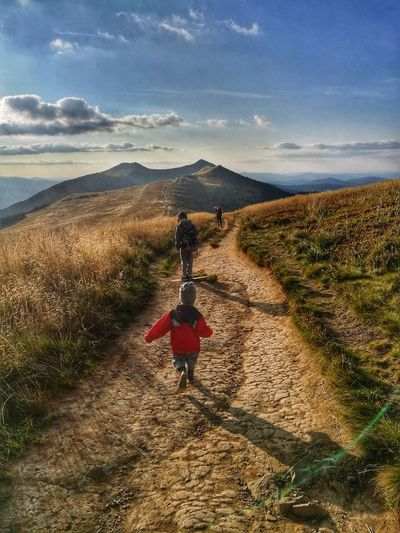Rear view of girl walking with dog on mountain against sky