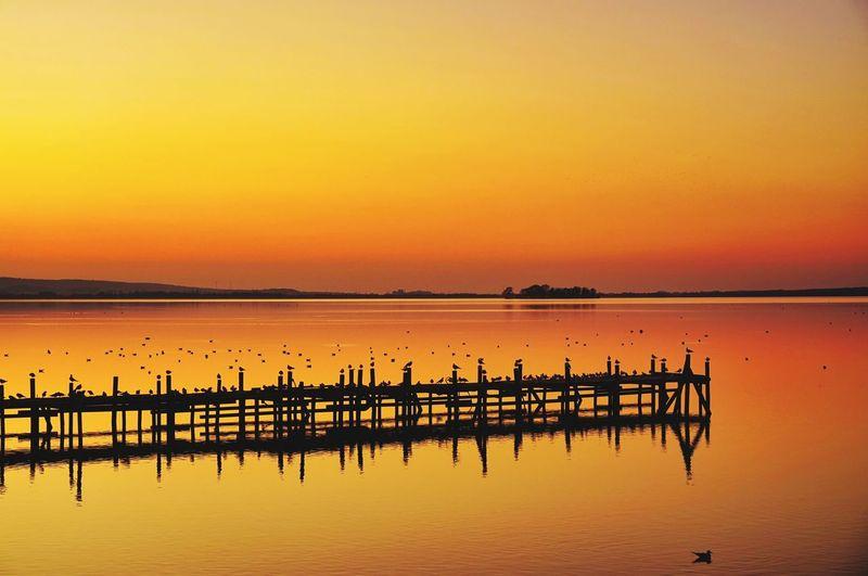 Pier on lake against orange sky