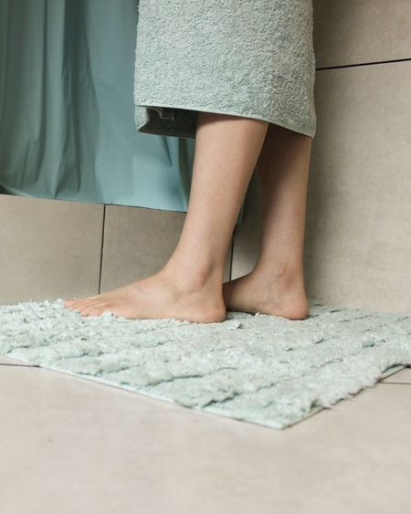 Low Section Of Woman Wrapped In Towel Standing On Rug At Bathroom
