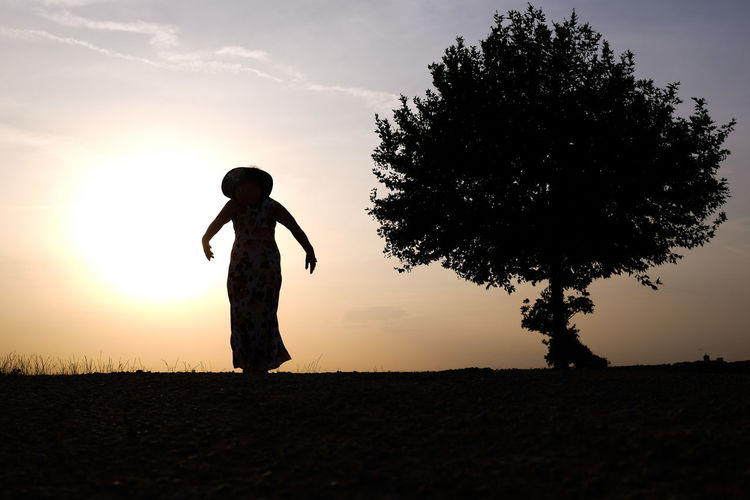 Beauty In Nature Day Field Full Length Growth Landscape Lifestyles Nature One Person Outdoors People Real People Scenics Silhouette Sky Standing Sunset Tranquil Scene Tree Women