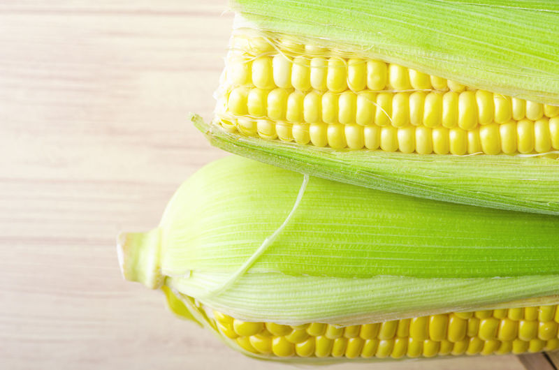 fresh raw sweet corn on the cob kernels over wooden background Corn Vegetable Food And Drink Still Life Table Yellow Wellbeing Sweetcorn Freshness Food Healthy Eating Green Color Corn On The Cob Close-up Indoors  No People Raw Food High Angle View Wood - Material Focus On Foreground Vegetarian Food