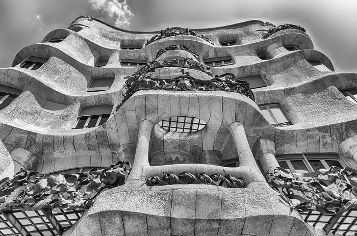 BARCELONA - AUGUST 9: Facade of the modernist masterpiece Casa Mila, aka La Pedrera, renowned building designed by Antoni Gaudi and iconic landmark in Barcelona, Catalonia, Spain, on August 9, 2017 Architecture Day Real People Low Angle View Built Structure One Person Sky Representation Lifestyles Outdoors Building Exterior Men Sculpture Nature Front View Human Representation Holding History Art And Craft