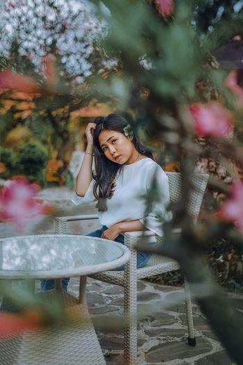 Portrait of smiling young woman against plants