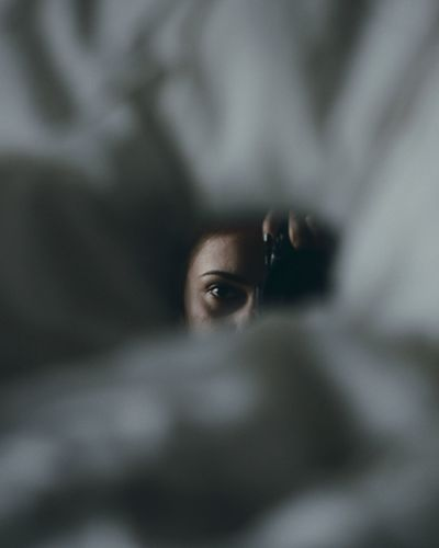 Portrait of young woman holding camera indoors