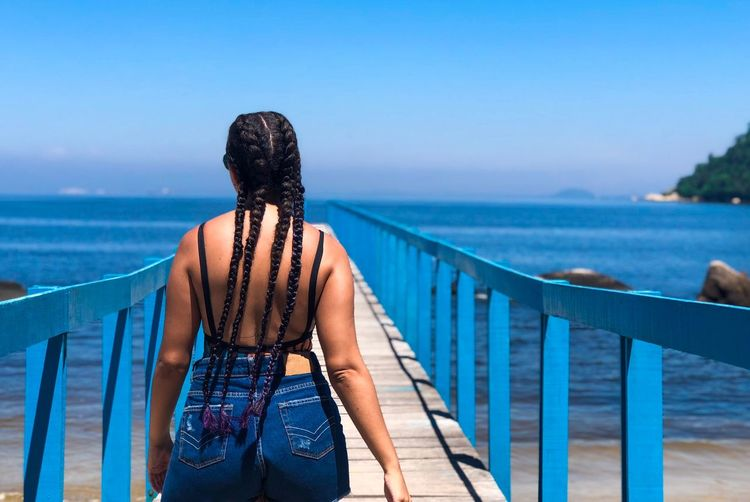 Rear view of woman with braided hair standing on footbridge against sea