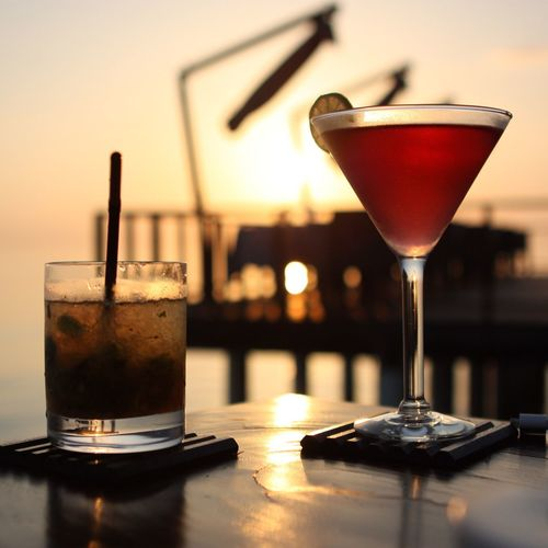 Close-Up Of Drink On Table Against Sky During Sunset