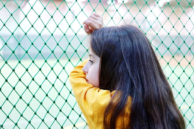 Close-up of thoughtful girl looking away by chainlink fence