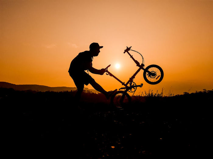 Silhouette man riding bicycle on land against sky during sunset