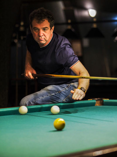 Mature man looking away while playing snooker