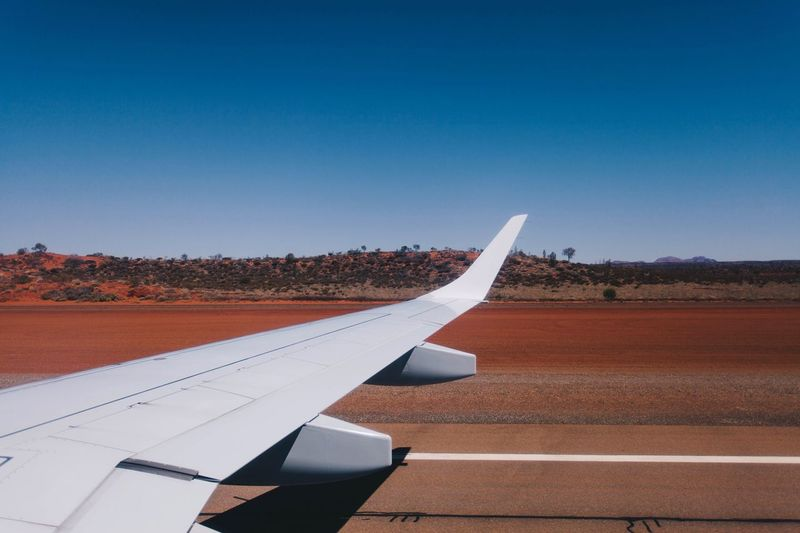 Cropped image of airplane on airport runway against clear blue sky