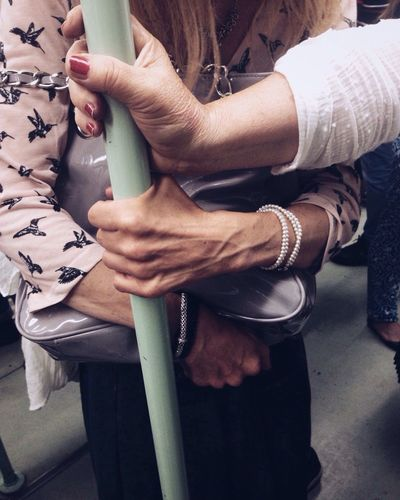 Midsection Of Women Holding Pole In Train