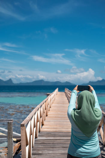 Outdoor portrait of woman in hijab taking photo of the scenery with her smartphone.