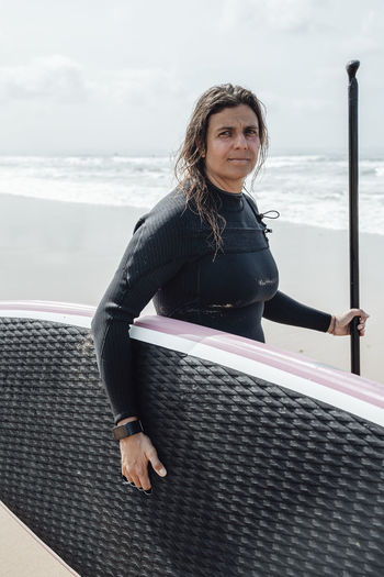Portrait of young woman standing by railing against sea