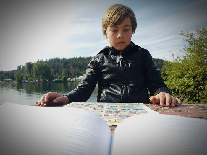 EyeEm Selects One Person Sitting Leisure Activity People Day Outdoors Males  Sky Young Man Lake Reading Reading A Book Fall Coeur D'Alene Cellphone Photography The Week On EyeEm The Funnies Comics Funny Pages Youth Our Future Leaders Water Beach EyeEmNewHere Inner Power The Portraitist - 2018 EyeEm Awards