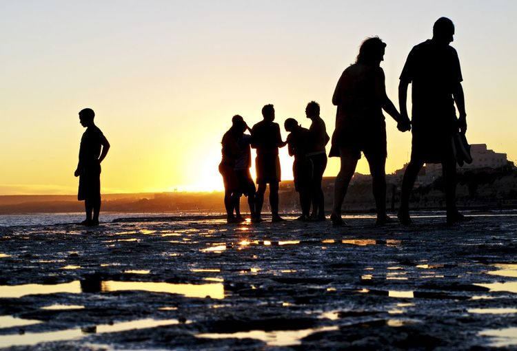 Silhouette People Standing On Shore At Beach Against Sky During Sunset